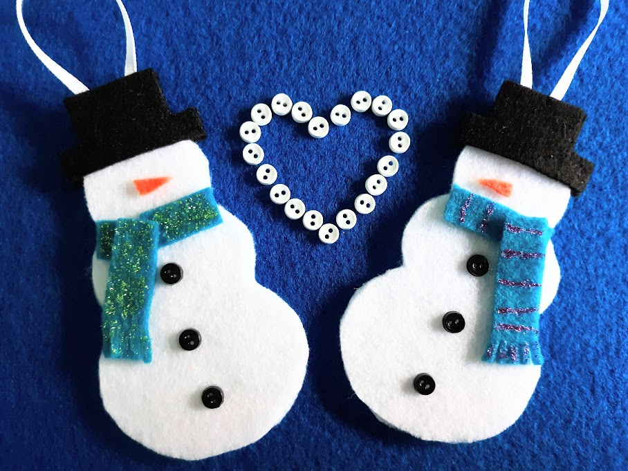 Two finished felt snowman ornaments laying on blue felt background with white mini buttons arranged in a heart between the two snowmen.