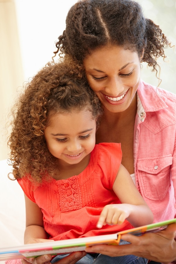 Black woman reading with daughter sitting in her lap, both smiling as little girl points at the page.