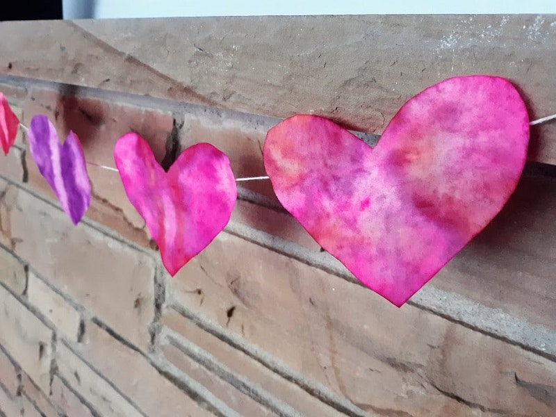 Pink and purple colored coffee filter hearts strung up as garland using twine on a brick mantel.