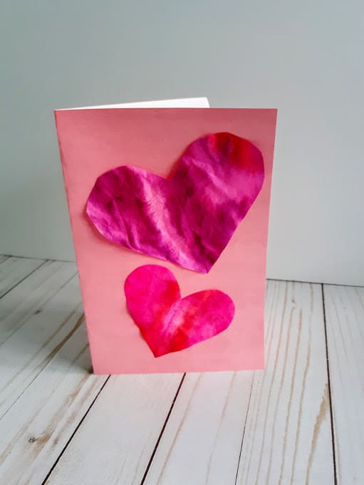 Homemade valentine card made with pink card stock and two different sized coffee filter hearts glued to the front.