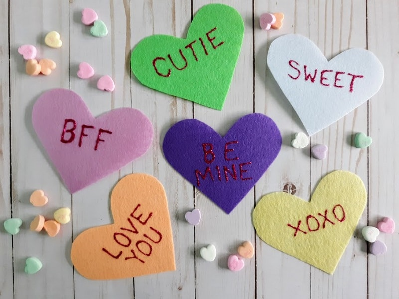 Six different colored felt hearts (pink, orange, purple, green, yellow, and white) with words written in glitter glue (BFF, Love You, Cutie, Be Mine, XOXO, Sweet) with candy conversation hearts spread out around them.