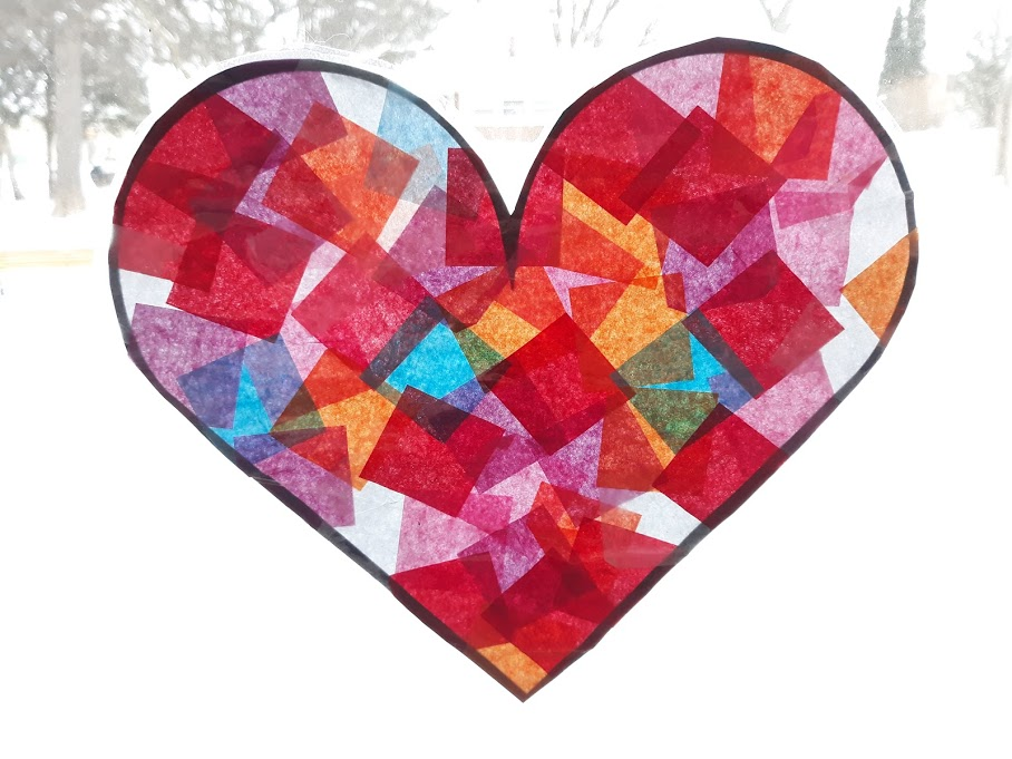 Completed heart suncatcher made with red, pink, purple, white, blue, and orange tissue paper and hung in a brightly lit window.