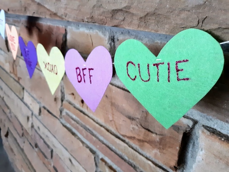 Close view from side angle of felt conversation heart banner hanging on mantel.