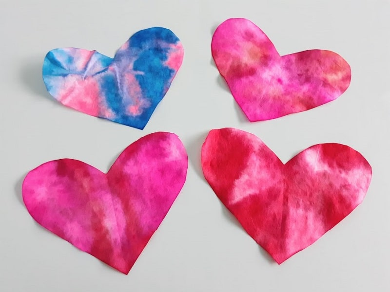 Four completed coffee filter hearts laying on an off white craft mat. One heart is blue and pink tie dyed and the other three are various shades of red and pink.