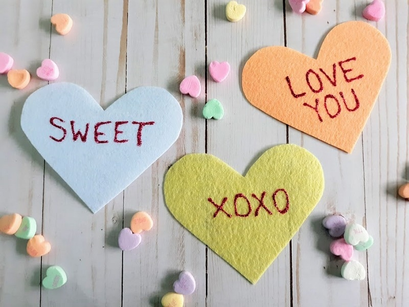 Close overhead view of three felt conversation hearts. White heart says Sweet, yellow heart says XOXO, orange heart says Love You. Small candy hearts sprinkled around the felt hearts on a light white wood background.