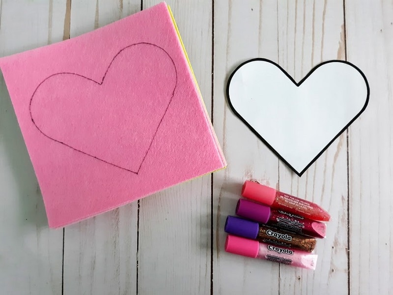 Heart pattern traced on pink felt and next to assorted glitter glue colors.