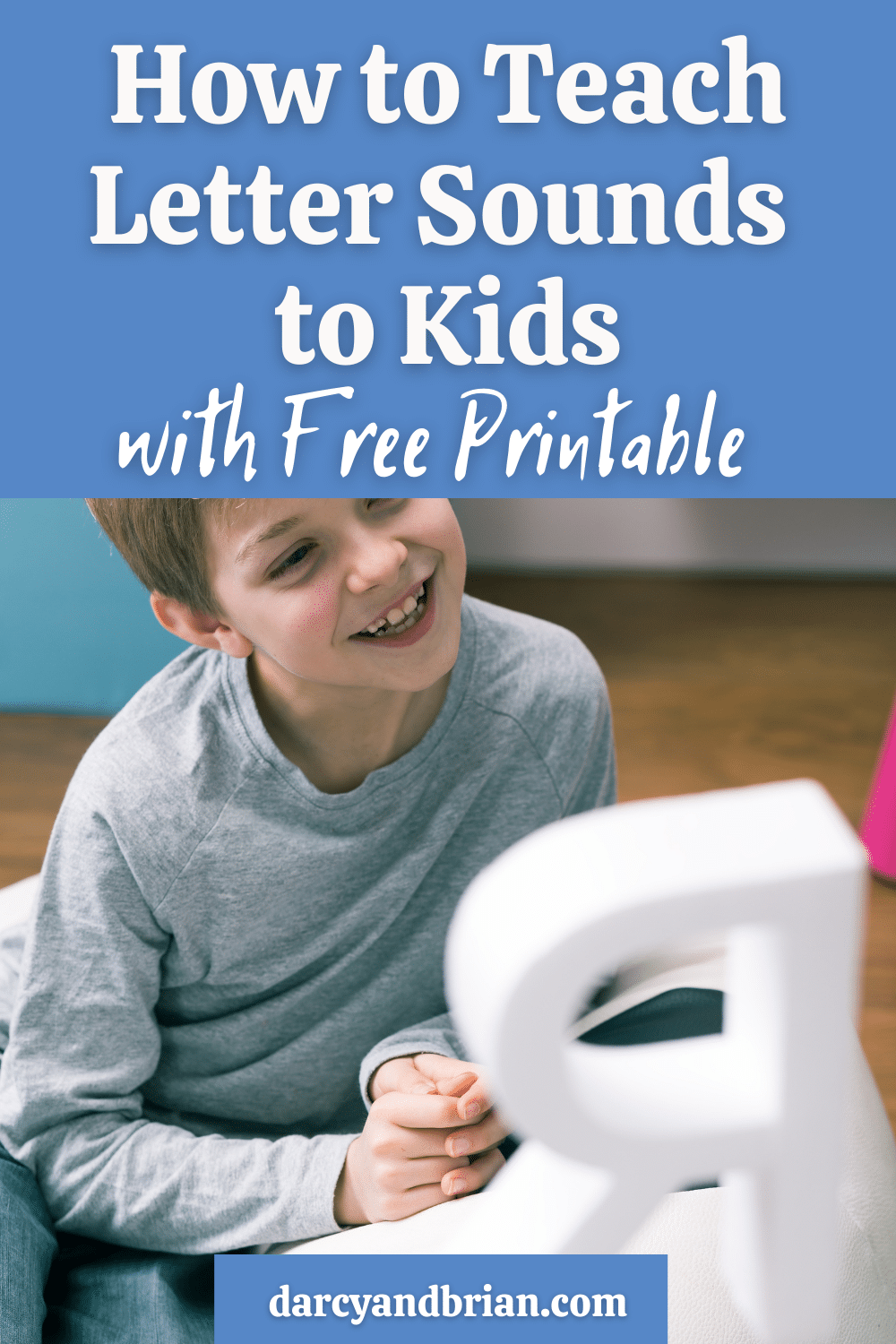 Light blue box with white text at top reads How to Teach Letter Sounds to Kids with Free Printable above photo of white boy in gray long sleeve shirt looking at a large white letter R and smiling.