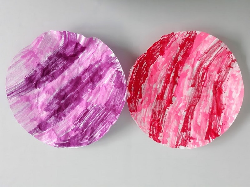 One round coffee filter colored with purple and pink markers laying next to another colored with red and pink markers.