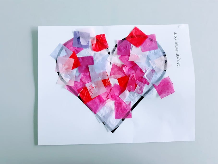 Overhead view of heart template covered with glued on tissue paper squares.