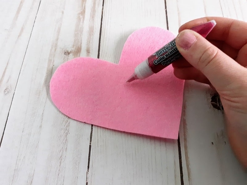 White girl's hand holding glitter glue getting ready to write and decorate pink felt heart.