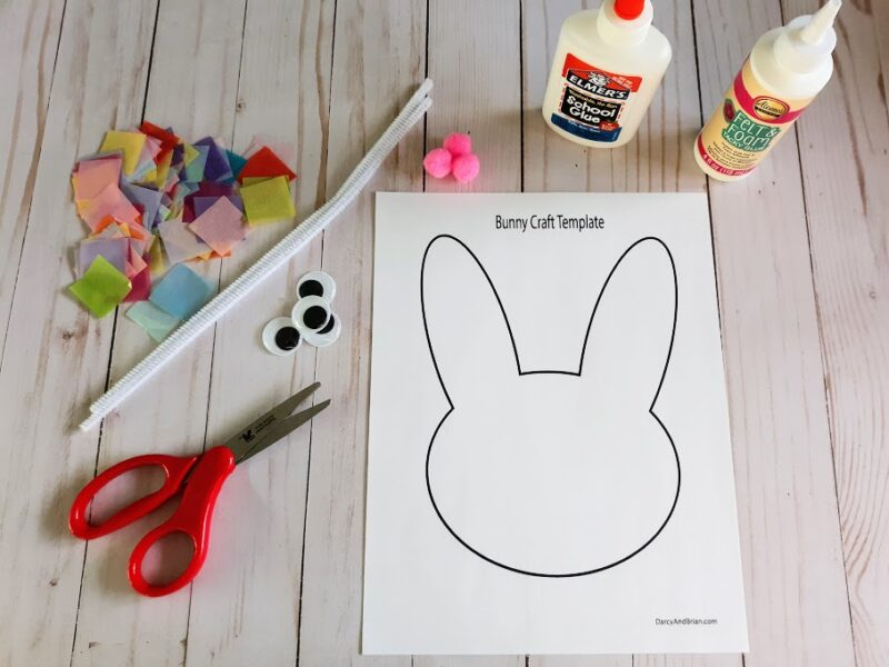 Overhead view of bunny template printed out and laying next to glue bottles, pom poms, tissue paper squares in a variety of colors, white chenille stem, googly eyes, and scissors with red handles.