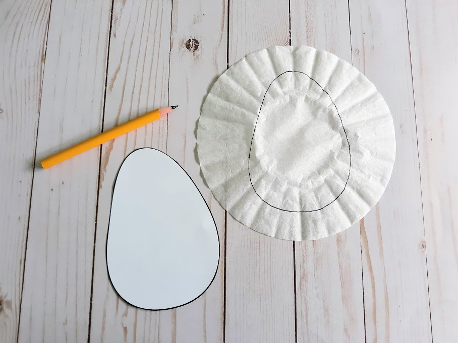 Cut out egg craft template next to a pencil and a coffee filter with traced egg shape drawn on it.