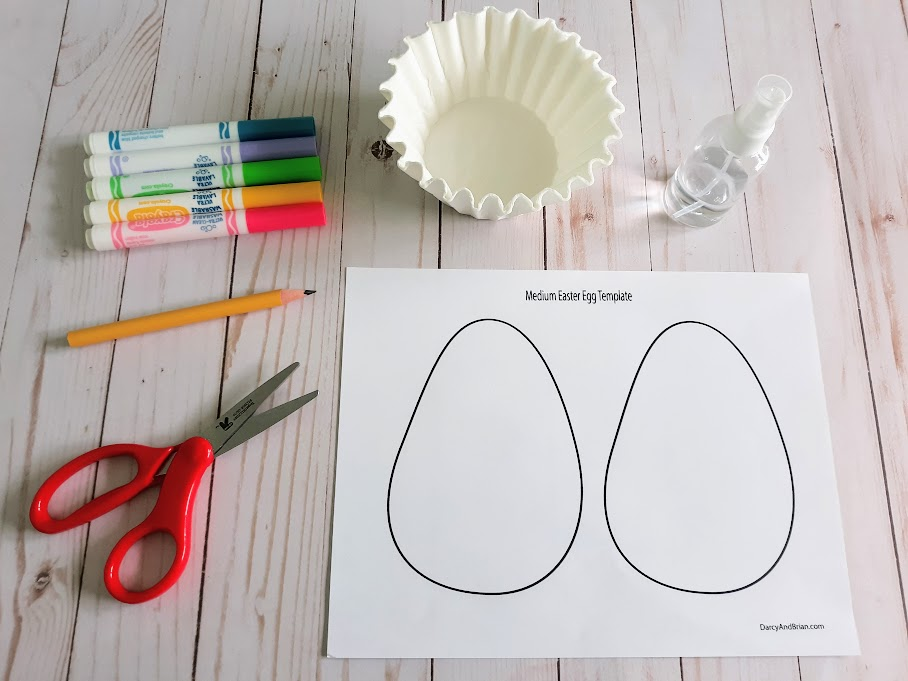 Overhead view of craft supplies to make coffee filter Easter eggs: Scissors, pencil, washable markers, coffee filters, spray bottle, and egg craft template printable.