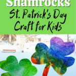 White and black text on green square on top half of image reads: Coffee Filter Shamrocks St. Patrick's Day Craft for Kids. Lower half of image shows one green and one rainbow tie dyed coffee filters cut into shamrock shapes in a bright wintery window.