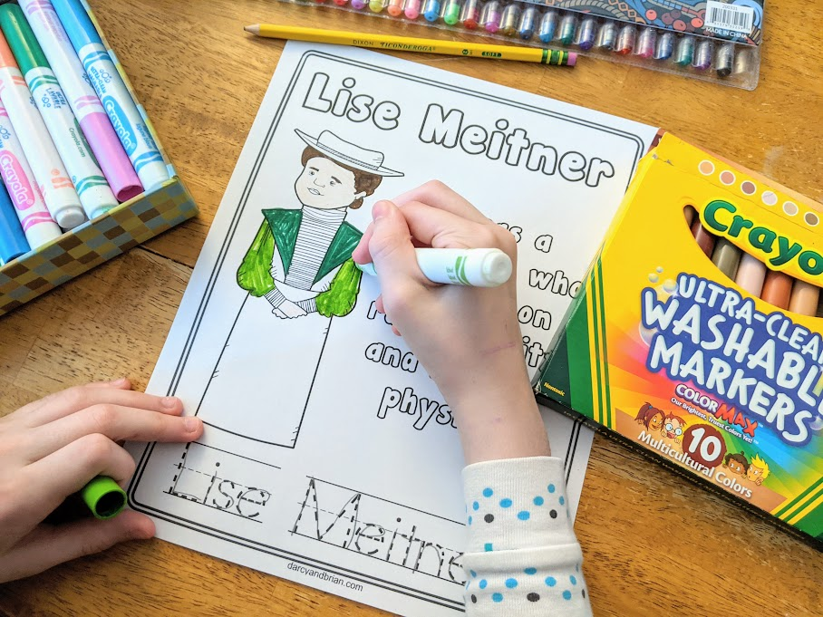Overhead view of white girl's hand holding a marker and coloring the printable page for Lise Meitner. Markers and gel pens are on the table around the paper.