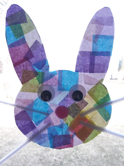 Tissue paper bunny suncatcher with eyes and whiskers in a brightly lit window, sun showing through it.