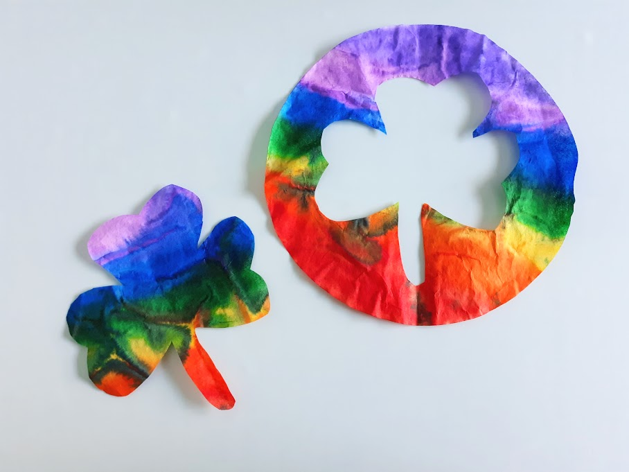 Rainbow colored coffee filter shamrock shape laying next to round filter with cut out in the middle.