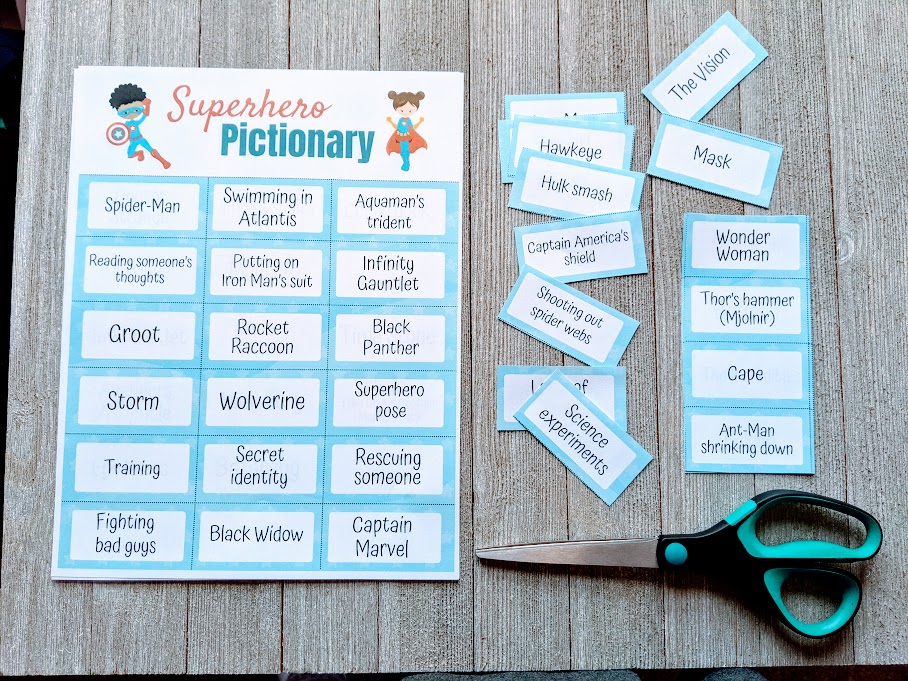 Overhead view of one full sheet of superhero pictionary prompts next to cut out clues and a pair of scissors on a dark gray wood background.