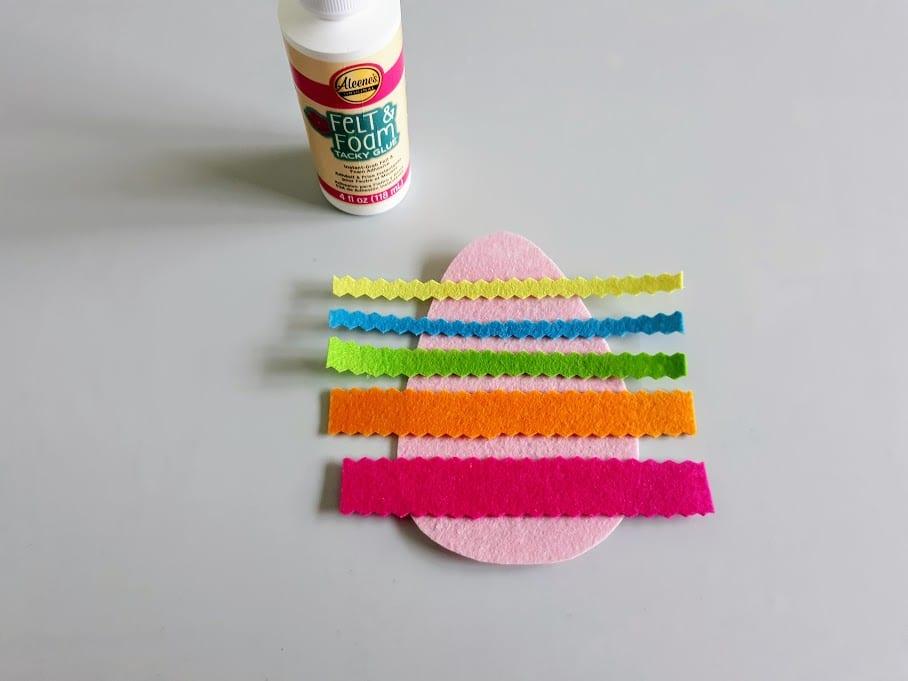 Bottle of felt glue next to pink felt egg shape with strips of felt glued across it.