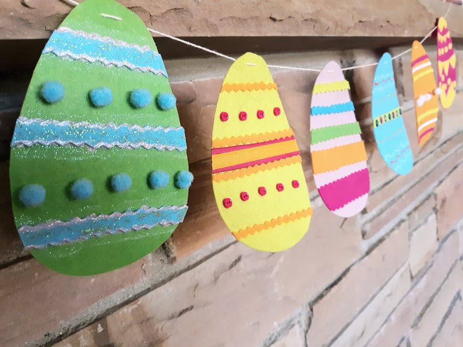 Multicolored felt eggs strung as a banner across a brick mantle.