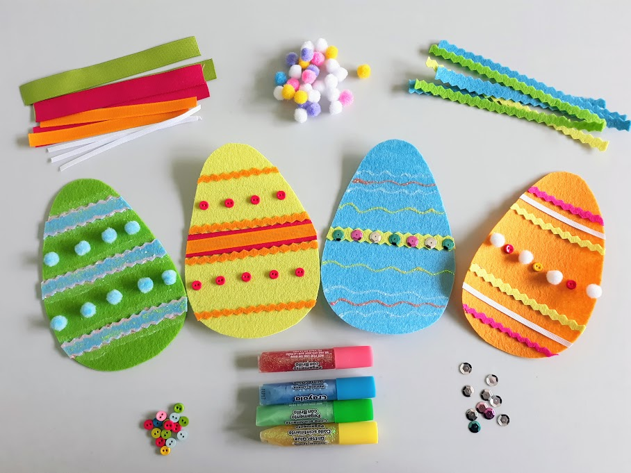 Overhead view of four completed felt Easter eggs with piles of different craft supplies around them such as felt, pom poms, sequins, and glitter glue.