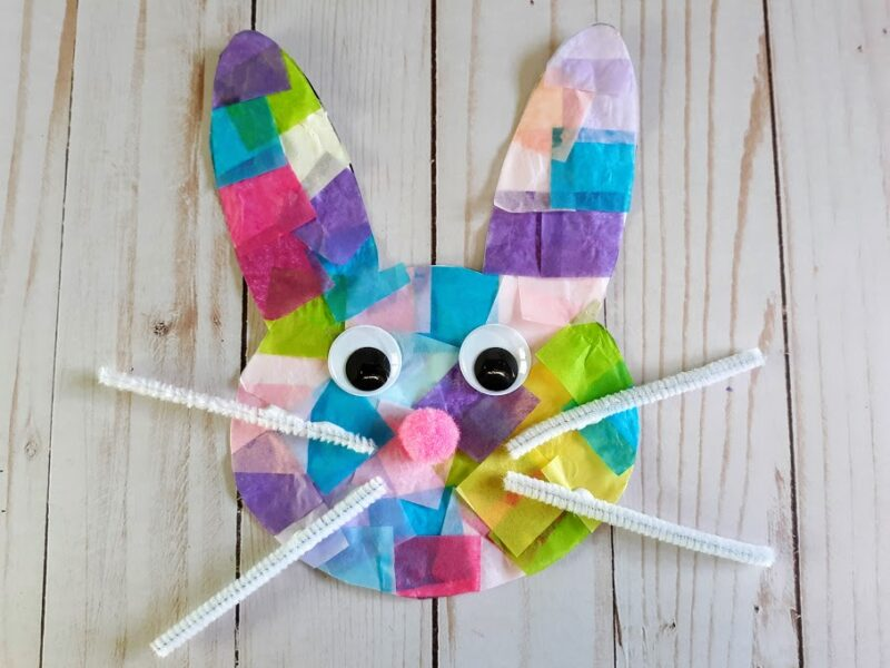 Overhead view of finished bunny suncatcher made with tissue paper, googly eyes, pink pom pom ball, and white pipe cleaner whiskers.