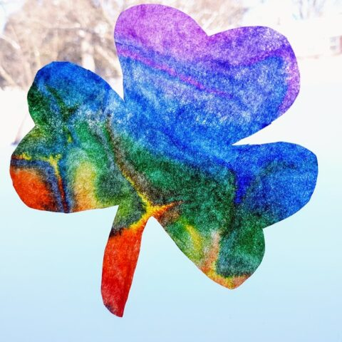 Completed rainbow colored coffee filter shamrock hanging in sunny, snowy window.