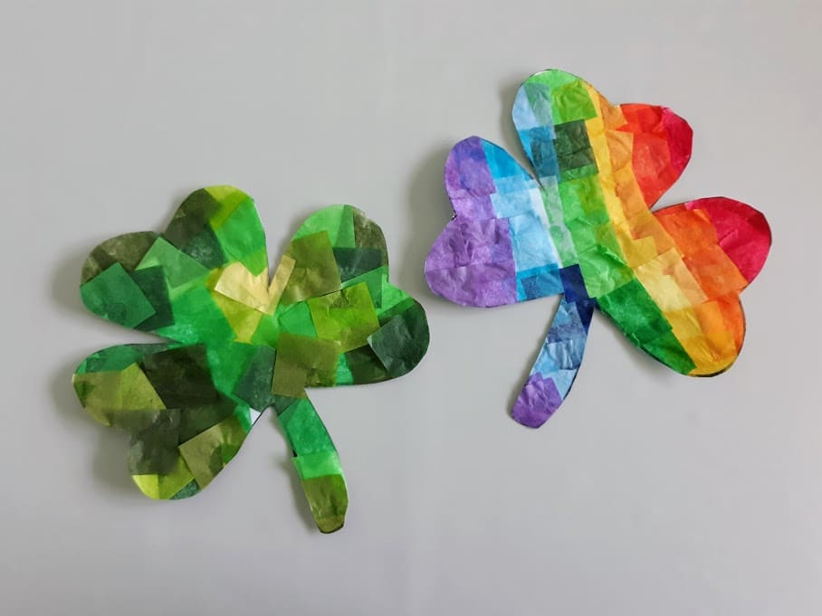 Two finished shamrock suncatchers cut out from template. Left one in various shades of green and the right one is rainbow.