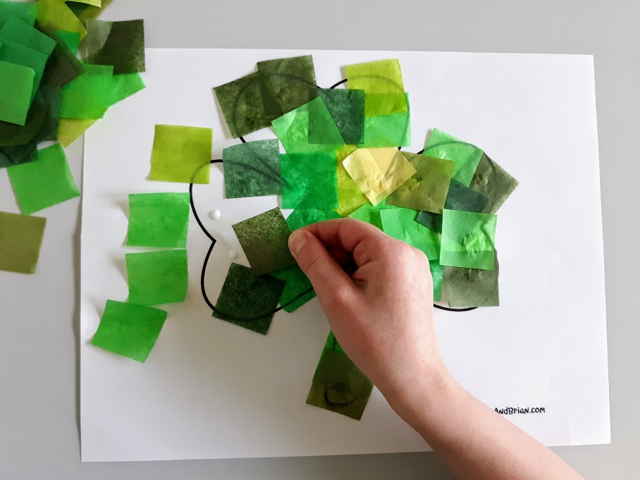 White child's hand gluing different shades of green tissue paper cut into squares onto printable shamrock template.