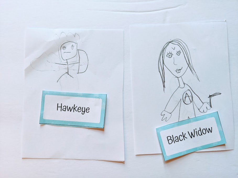 Kids' drawings of Hawkeye and Black Widow with the game word card by each picture.