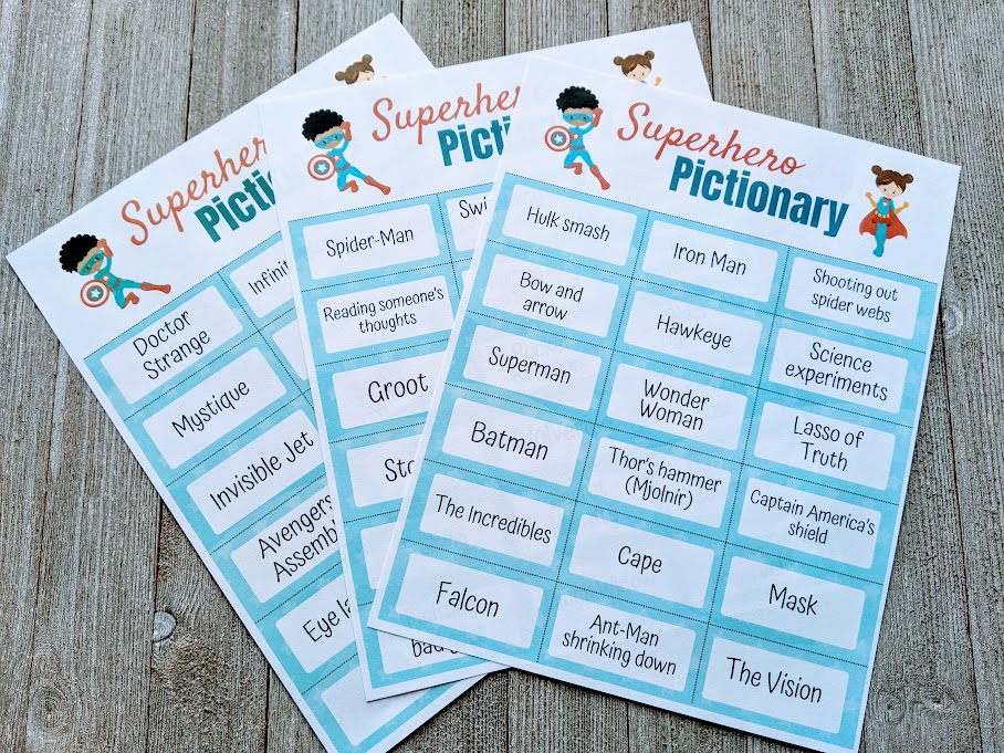 Three pages of superhero themed pictionary clues printed out and fanned out over a dark gray wood background.