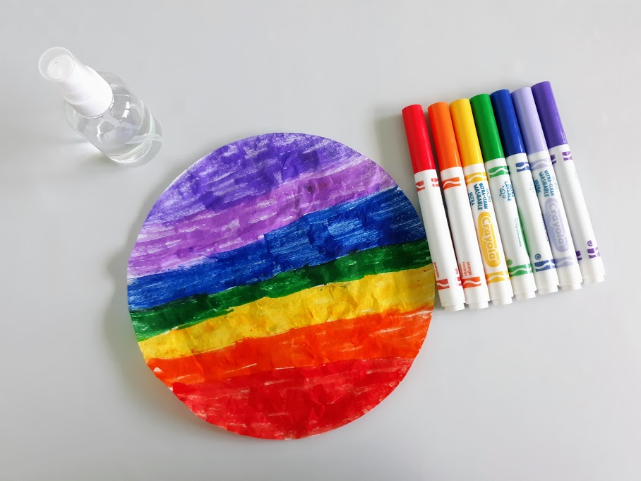 Overhead view of round coffee filter colored in a rainbow pattern. Markers and water spray bottle are next to the filter.