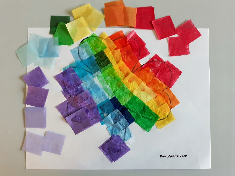 Tissue paper squares arranged in rainbow order around printable shamrock template covered in glued on tissue paper.