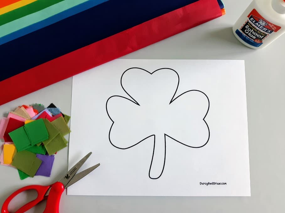 Shamrock template printout laying on craft table with scissors, tissue paper, and glue around it.