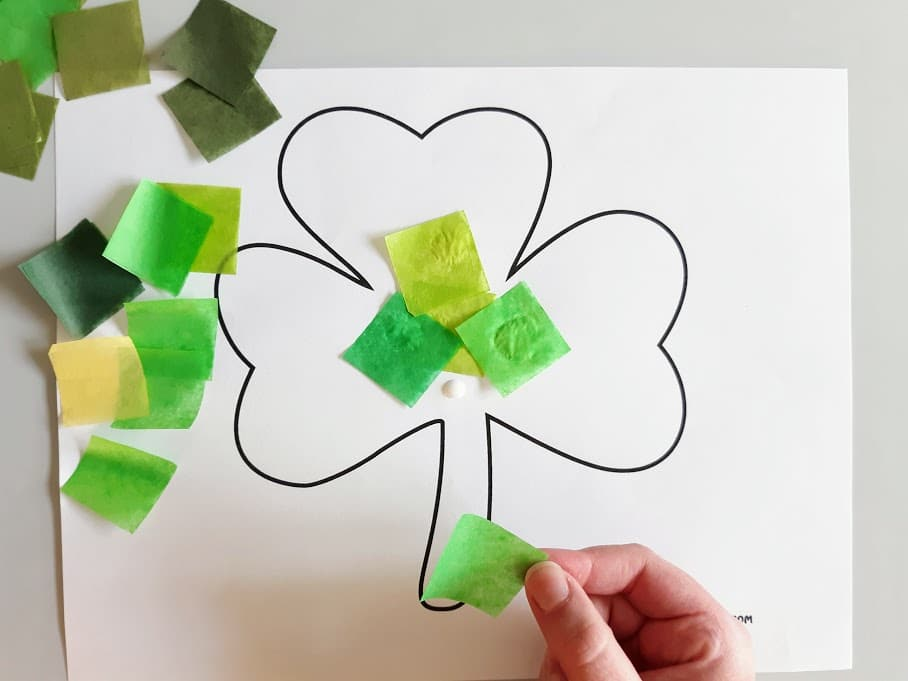 Pieces of cut up green tissue paper scattered on the left side of shamrock template. White child's hand gluing tissue paper to the shamrock.