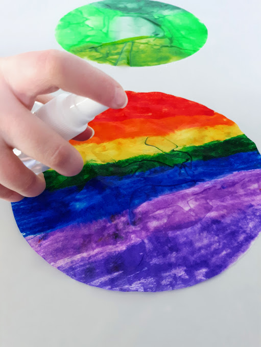 White girl's hand holding small spritz bottle and spraying rainbow colored coffee filter with water. A wet green colored coffee filter is farther in the back.