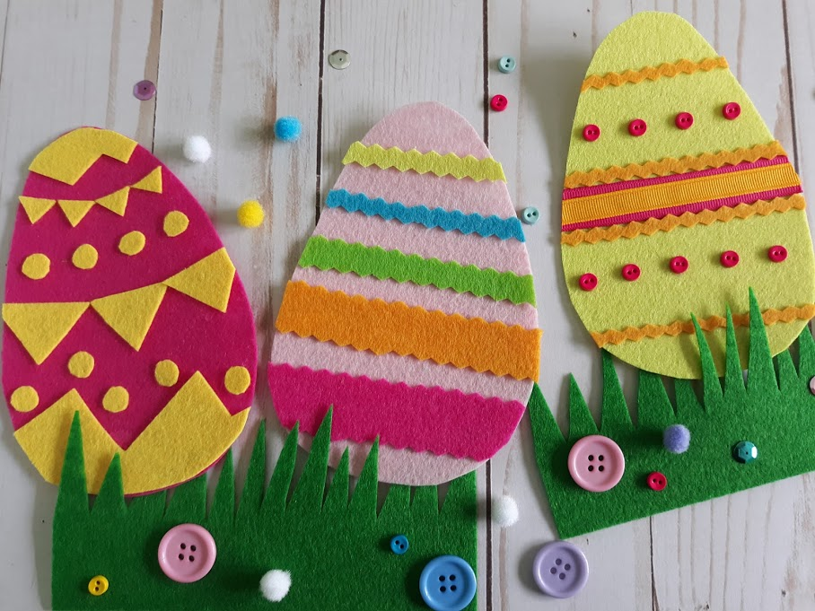 Overhead view of three completed felt Easter eggs decorated with felt and mini buttons and displayed in green felt cut to look like grass.