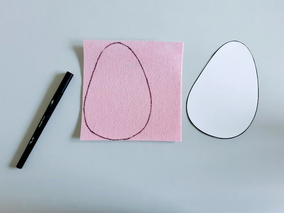 Egg template cut out and traced on a pink felt square.