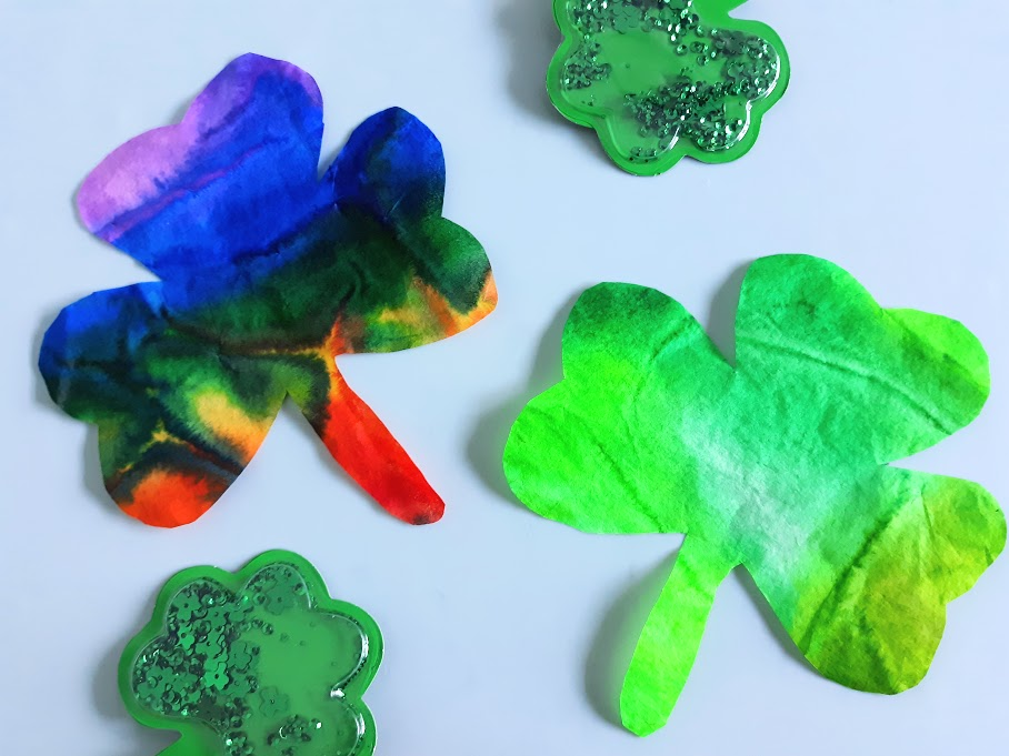 Finished rainbow and green coffee filter shamrocks laying on top of craft mat next to small plastic shamrocks.
