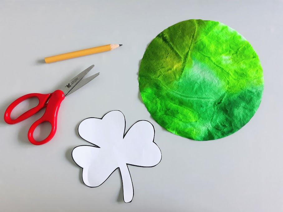 Overhead view of a pencil, red handle scissors, cut out shamrock template, and round green colored coffee filter.