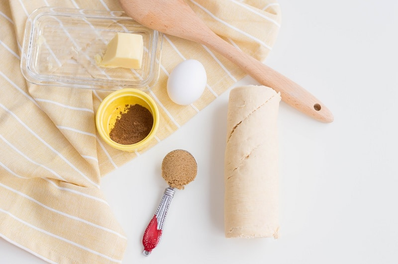 Unwrapped butter, one egg, small yellow bowl of cinnamon, measuring spoon full of brown sugar, roll of crescent dough removed from packaging, and wooden spoon arranged on yellow and white kitchen towel and white counter.
