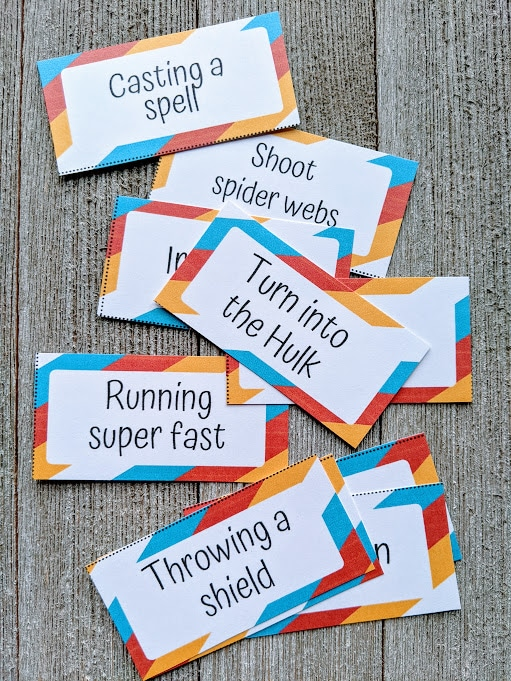 Close overhead view of about eight superhero charades clues cut out from the printable set. Each card has a red, orange, blue, and white border with the word prompt text in the middle. Visible clues include: casting a spell, turn into the Hulk, running super fast, and throwing a shield.