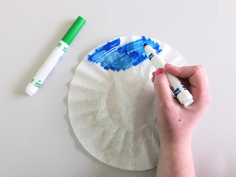 Overhead view of white girl's hand coloring coffee filter with blue washable marker. Green marker laying on the left side of the filter paper.