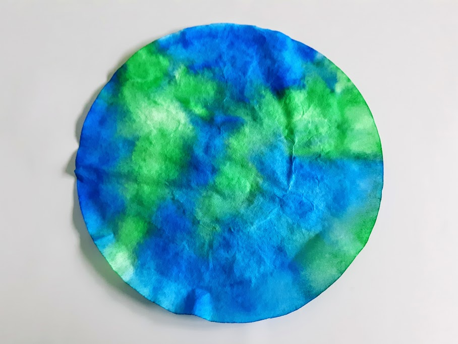 Dry coffee filter colored green and blue like Earth.