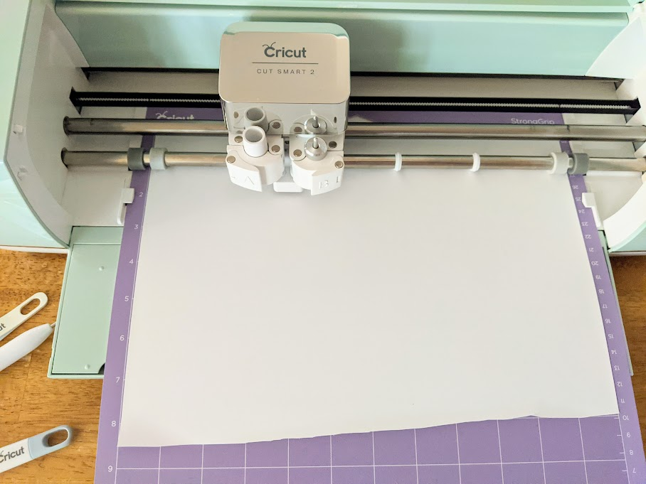Mint Cricut Explore Air 2 cutting machine open with purple mat loaded with white iron on vinyl. Blade is cutting design.