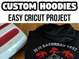 Black and white text says DIY Dragons & Dice Custom Hoodies Easy Cricut Project above photo of folded black hoodie showing design on the back with dragons, dice, and Is it Saturday yet? Hoodie is next to Cricut EasyPress 2 on a table.