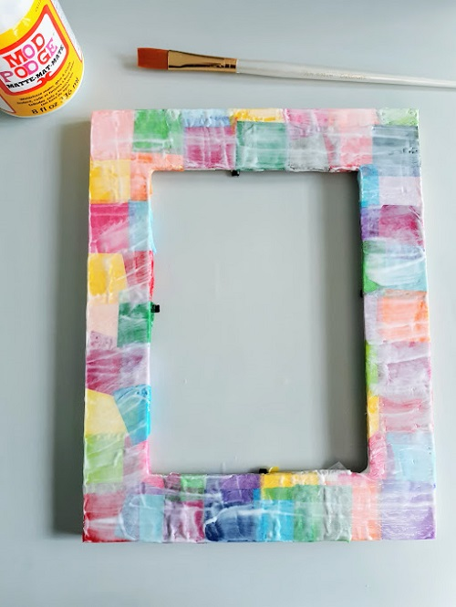 Overhead view of photo frame covered in tissue paper squares with edges fixed so none are hanging over, and covered in a coat of mod podge. A paint brush and bottle of mod podge are set down near top of frame.