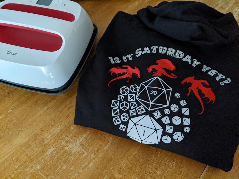 Completed custom hoodie with dragons and dice folded on table next to EasyPress 2.