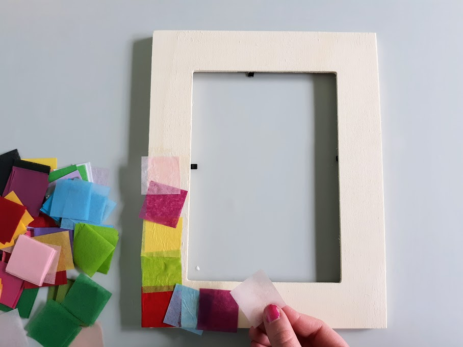 Overhead view of white girl's hand applying tissue paper square pieces to wood picture frame.
