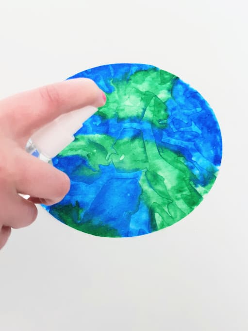 White girl's hand with small spray bottle spraying water on coffee filter colored to resemble Earth.